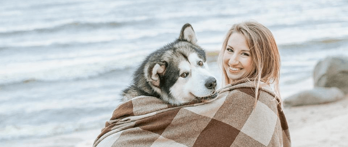 una ragazza sulla spiaggia col suo cane husky