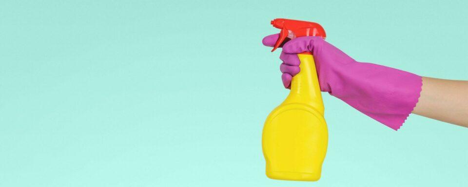 una mano con un guanto di gomma e un detersivo