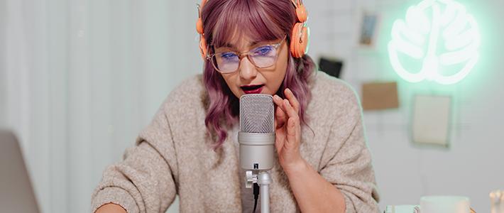Una ragazza con un paio di cuffie arancioni, i capelli viola, che parla a un microfono