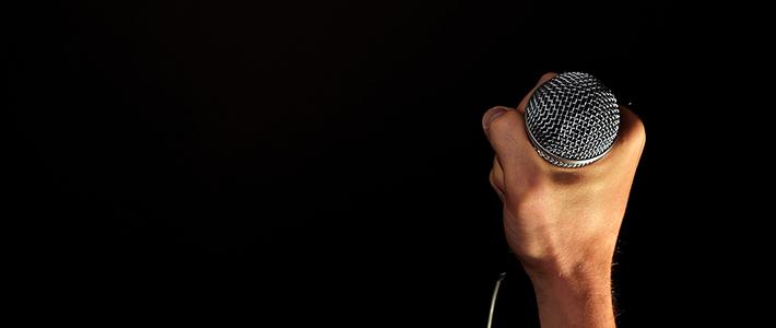 Una mano destra che impugna un microfono