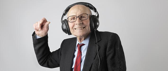 Un signore anziano in giacca e cravatta che indossa un paio di cuffie nere