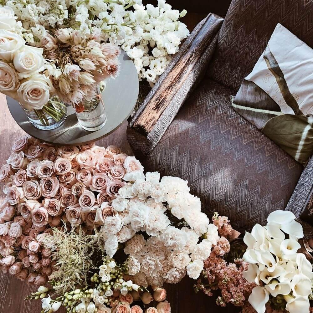 una poltrona circondata da mazzi di fiori rosa