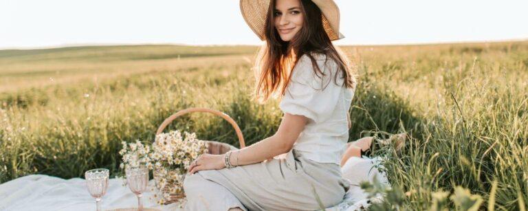 una ragazza su un prato che fa un picnic