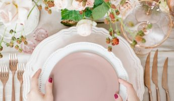 Crop top view of woman setting table with beautiful and elegant kitchenware and flowers.