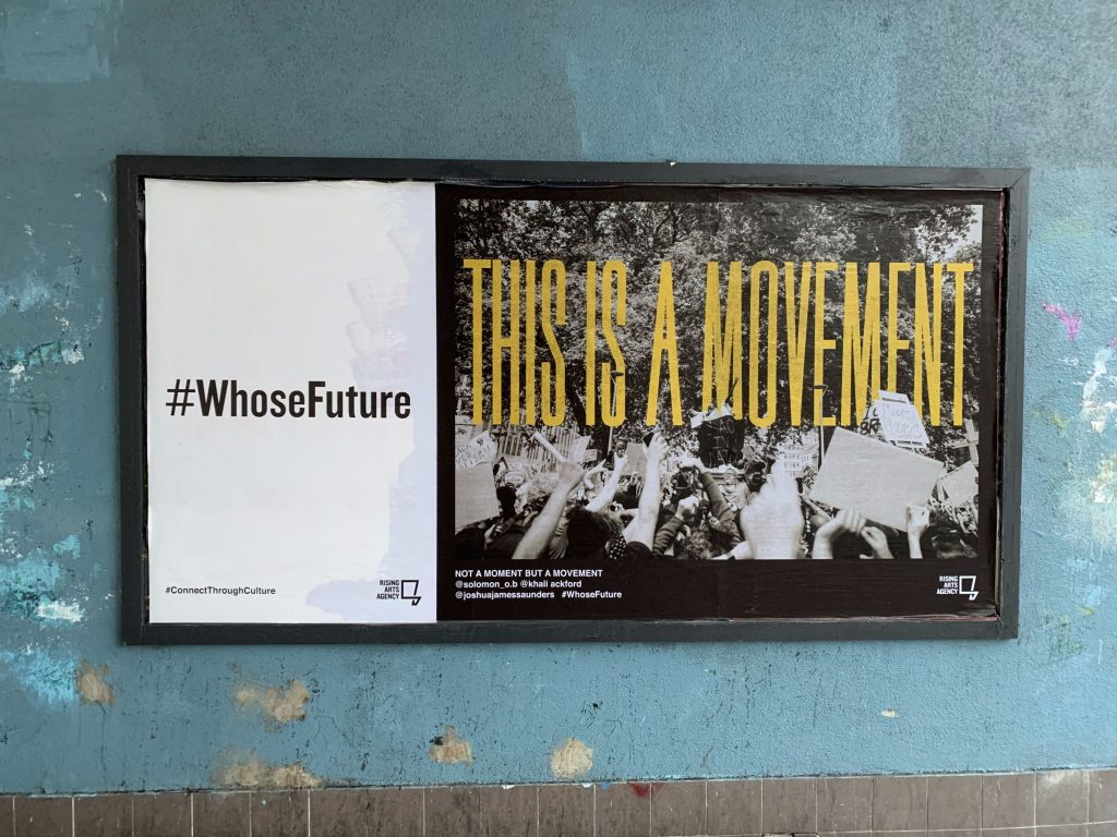 A #WhoseFuture campaign billboard which displays an edited black and white photograph of the empty Colston plinth at the Bristol BLM protest in June 2020, with the words 'This is a movement' overlayed in yellow