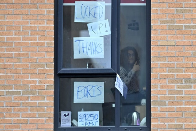"""Photograph of a student in halls with sign posted on the windows that reads 'Locked up! Thanks Boris £9250 + rent"""""""