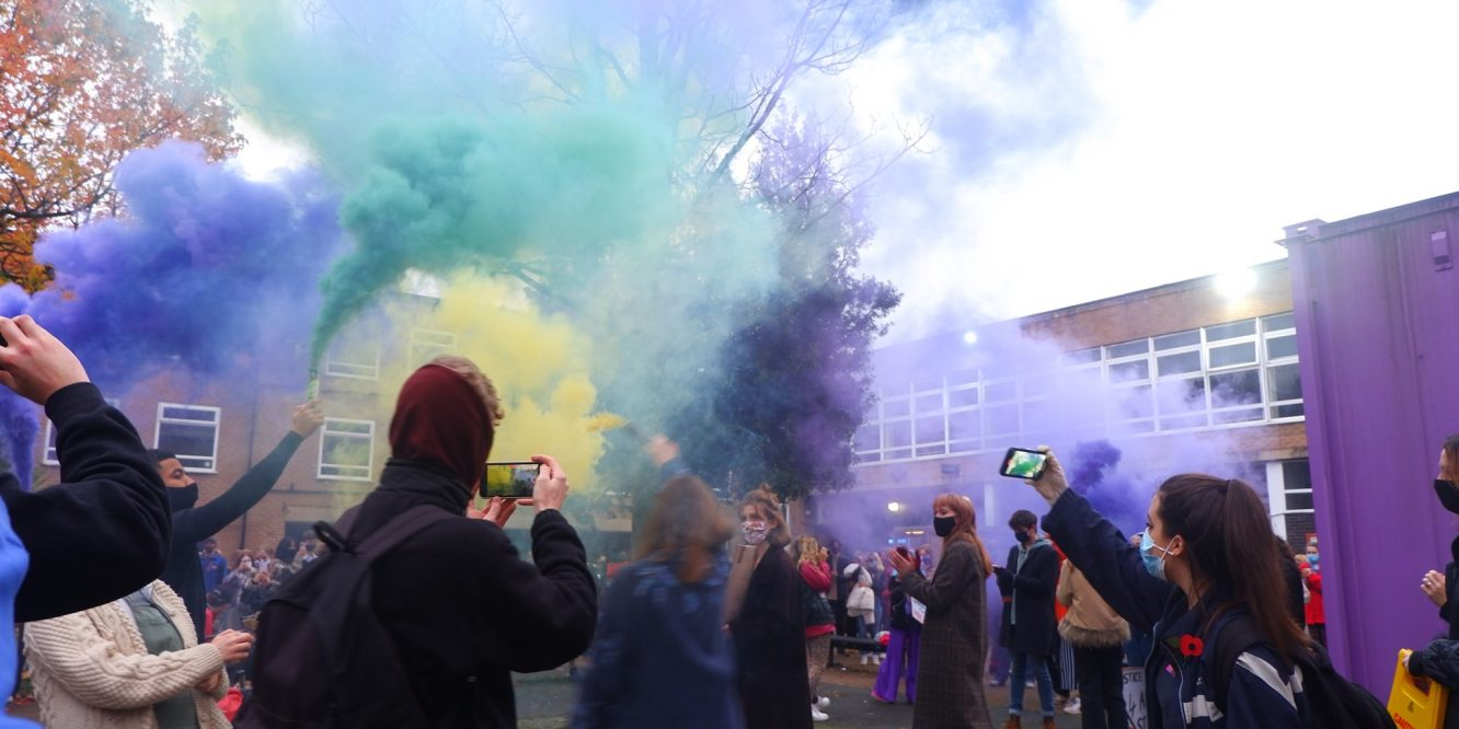 Students on the University of Manchester campus in Owen's Park holding up cans of multi-coloured smoke