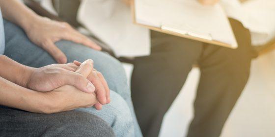 Samtale: Et par som holder hender samtaler med en person