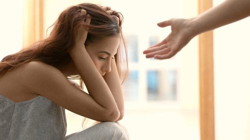 En kvinne som holder hendene til hodet og en hånd som strekker seg mot henne