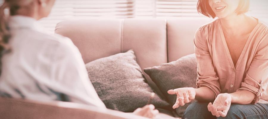 To kvinner som sitter og samtaler