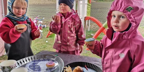 De tre barna i regntøy, Snapp, Storkfrøken og Snipp spiser kake.