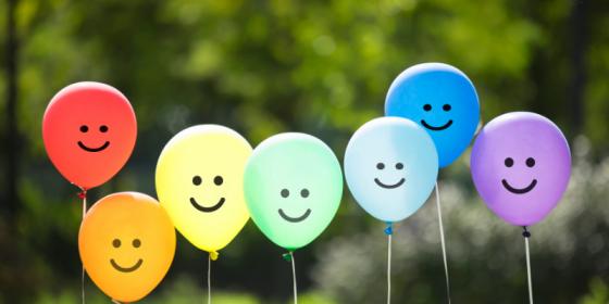 7 ballonger i regnbuens farger. På tegnet smileansikter. Grønn vegetasjon i bakgrunnen