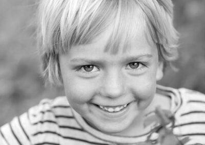 01-boerneportraet-fraek-dreng-kigger-smilende-frem-ersted.photo.jpg