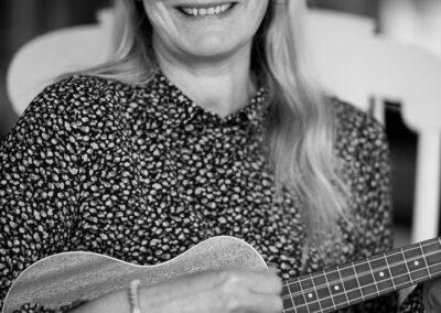 06-Kvinde-i-40erne-med-ukulele-spiller-smiler-ersted-photo-musikerportraet