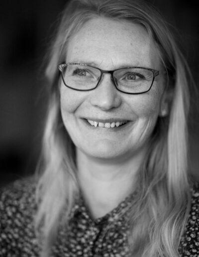 09-portraet-af-musiker-kvinde-i-40erne-med-briller-smiler-ersted-photo