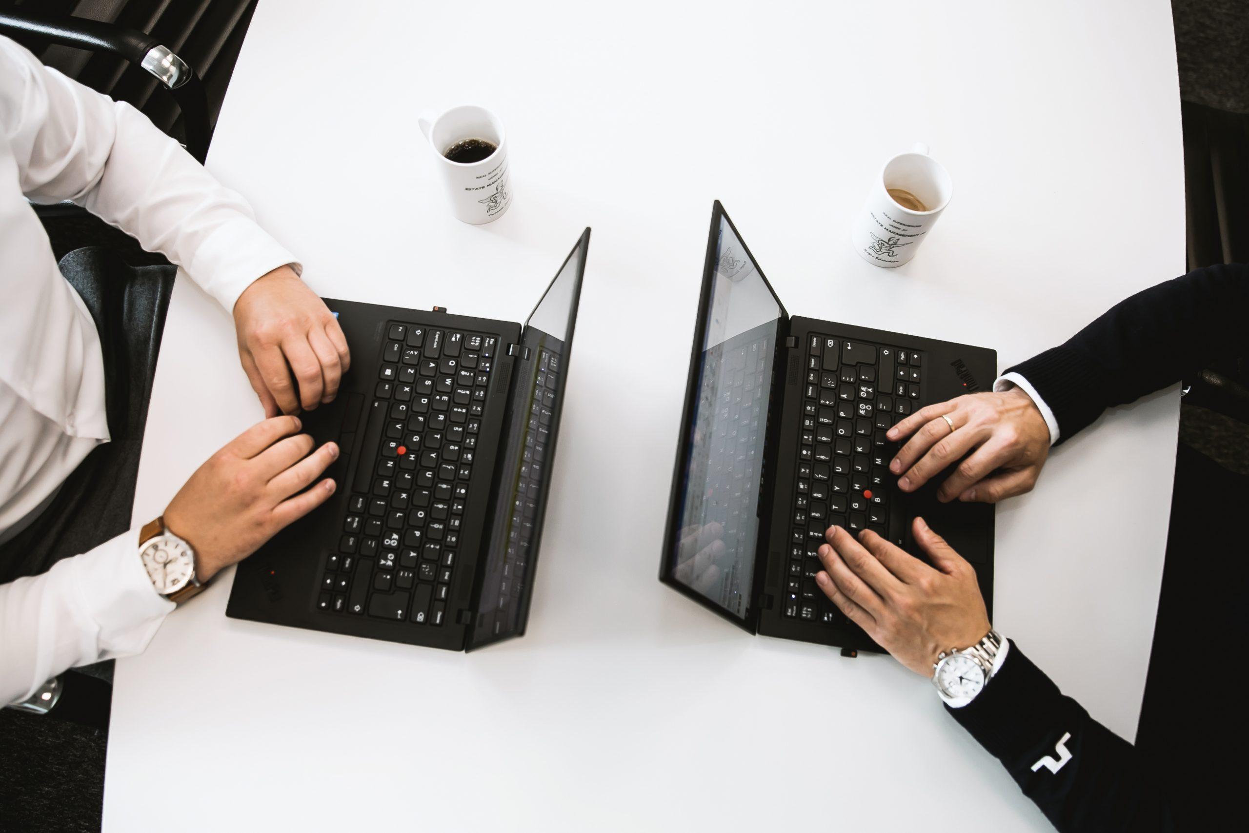 To personer som jobber på PC og drikker kaffe