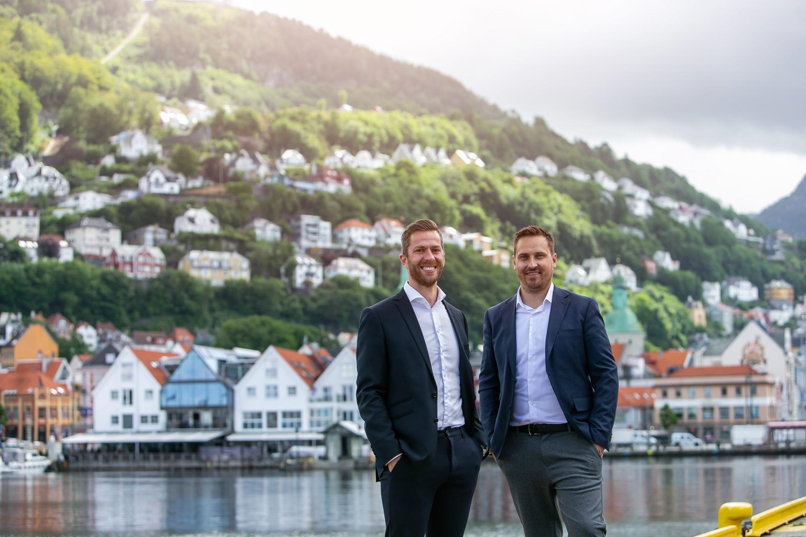 To personer står på Strandkaien med utsikt mot Zachariasbryggen, Fløyen og Skansemyren i Bergen.
