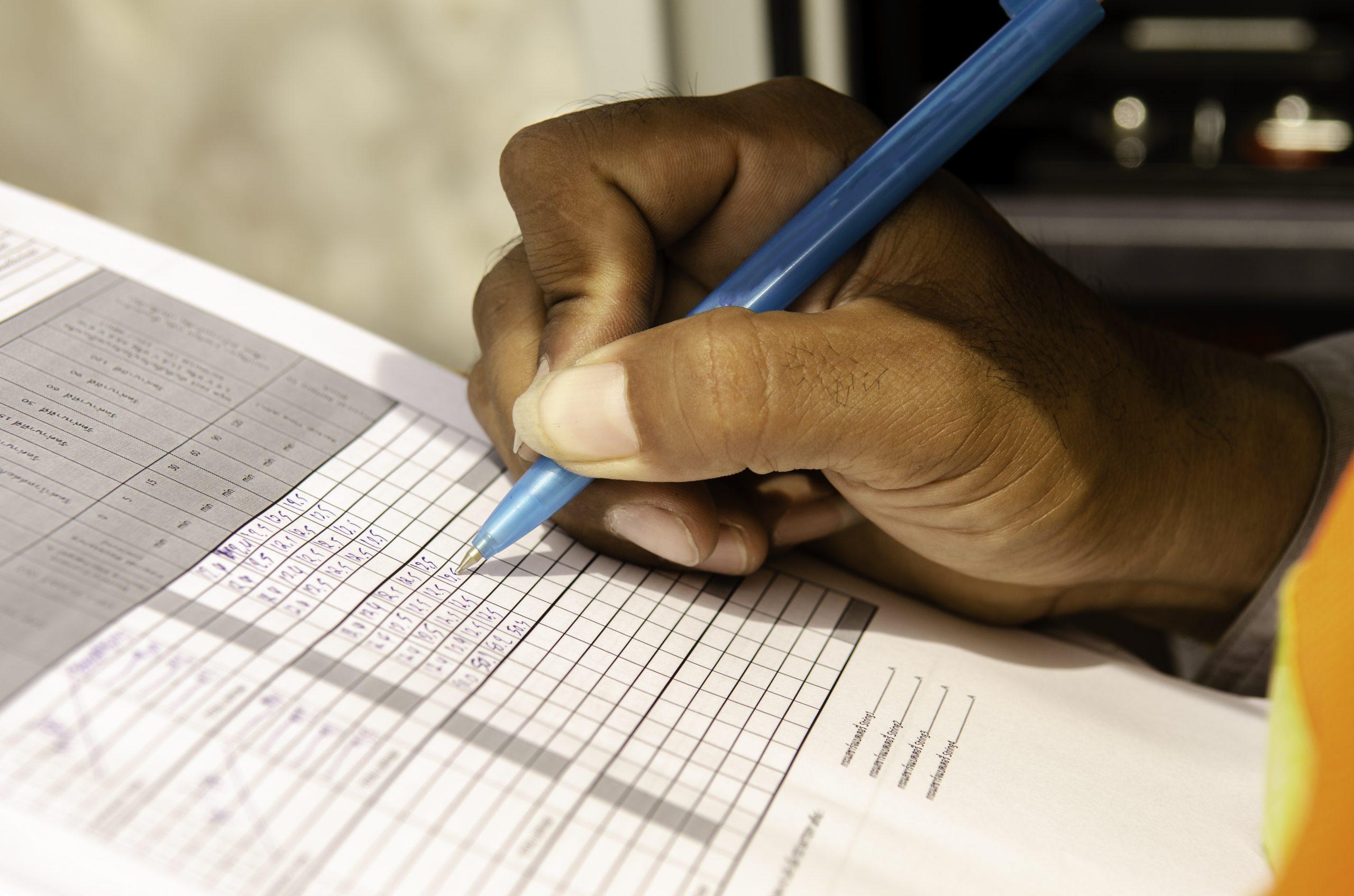 Nærbilde av en person som fyller ut sjekklister for kvalitet og gode rutiner