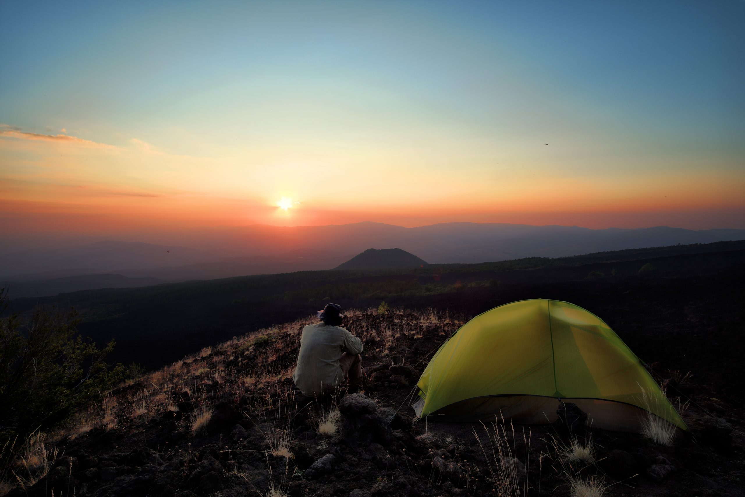 Turgåer med hatt som ser på solnedgangen oppe på fjellet.