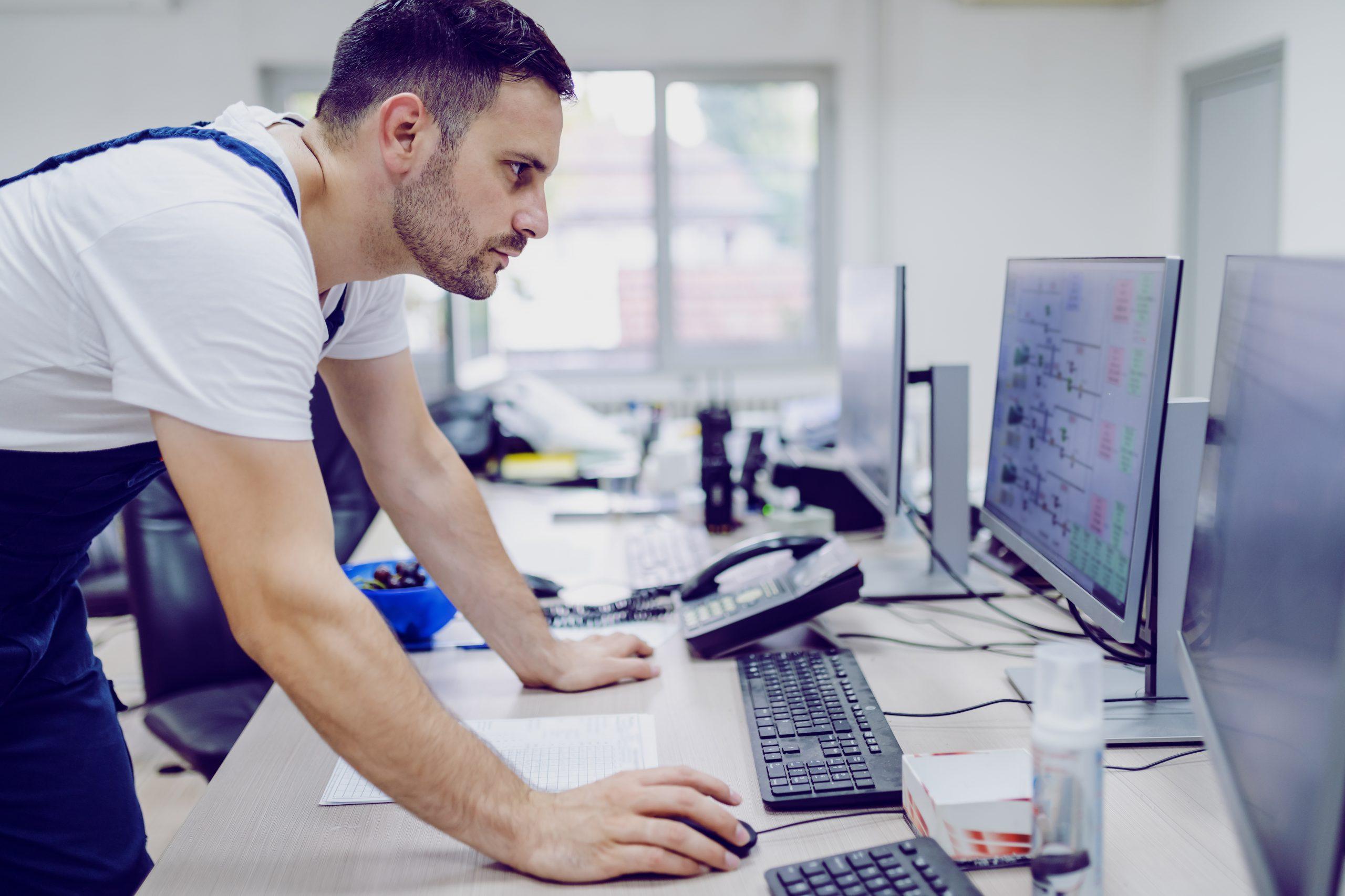 Sidevinkel av en seriøs arbeider som bruker datamaskin i kontrollrom