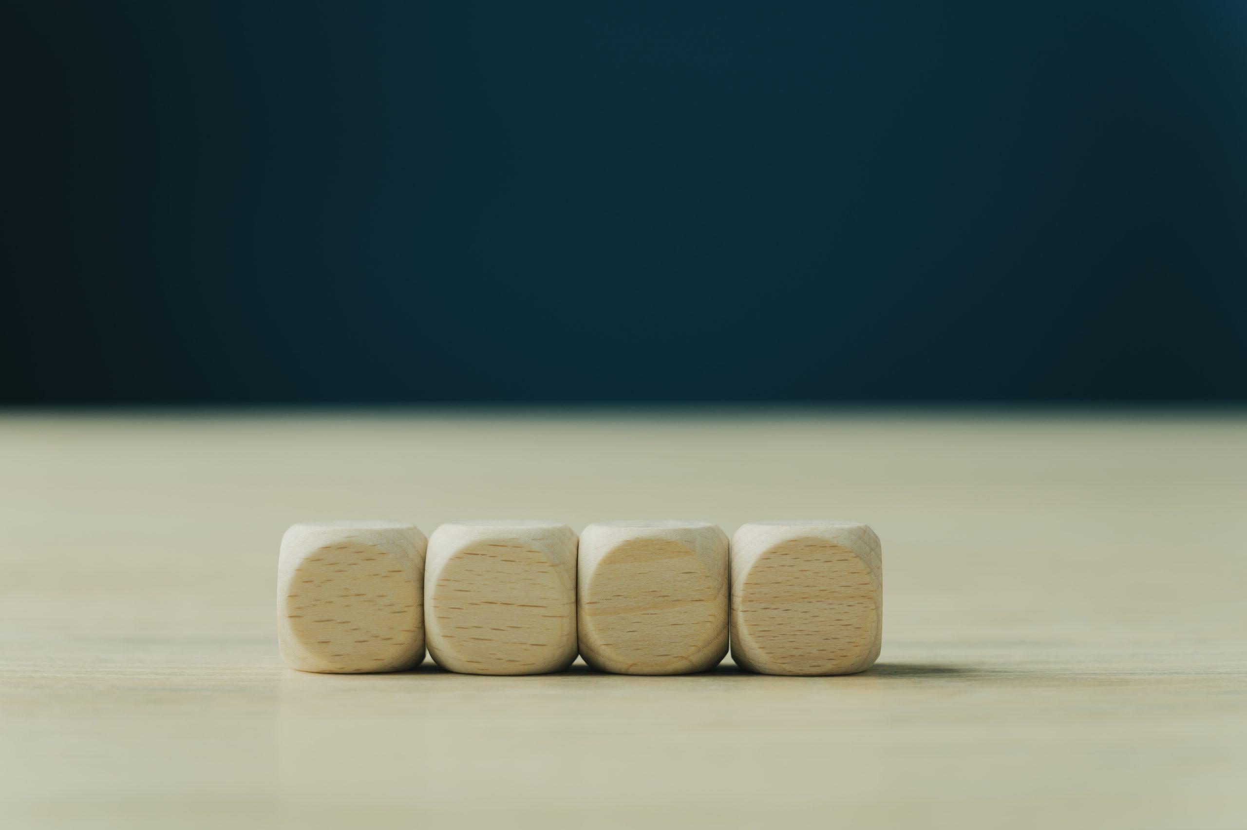 Fire blanke tre-terninger plassert ved siden av hverandre for å illustrere grunnmur