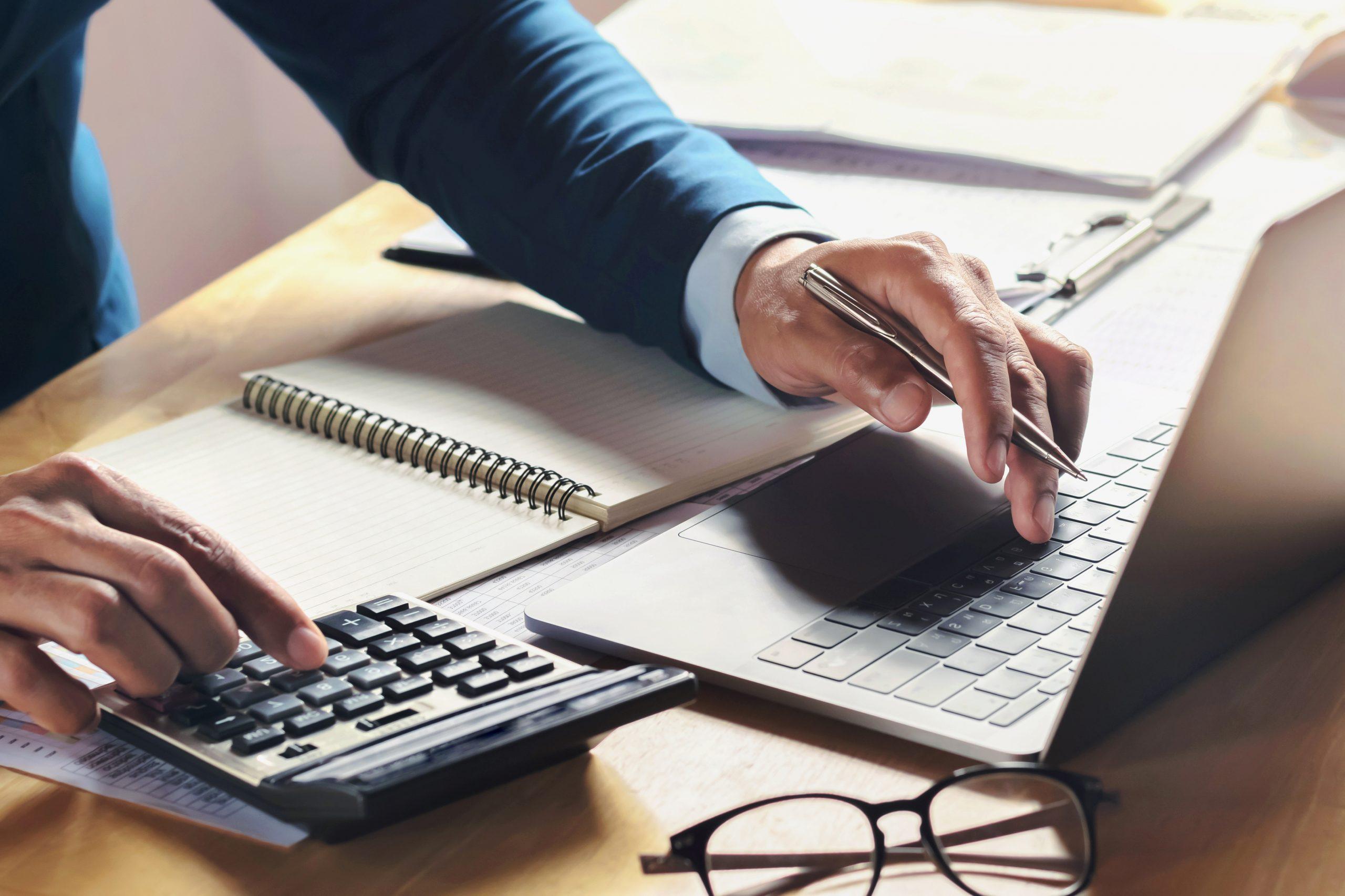 En forretningsmann som regner ut på kalkulator og datamaskin hva det koster å leie næringslokaler