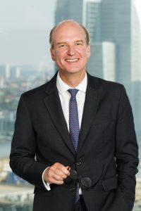 Vanguard Deutschland-Chef Sebastian Külps vor einem Wolkenkratzer, Interview mit dem ETF-Yogi über das Unternehmen Vanguard, Anlageberatung und neue ETFs