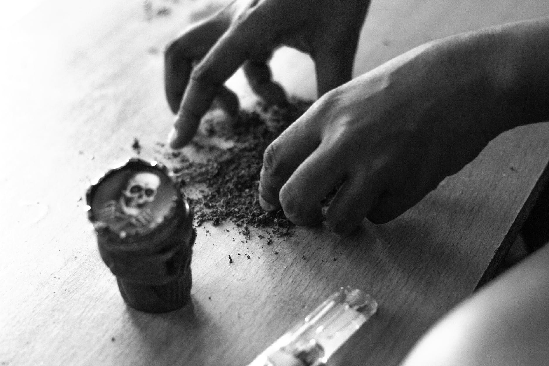 faceless man rolling up cannabis joint
