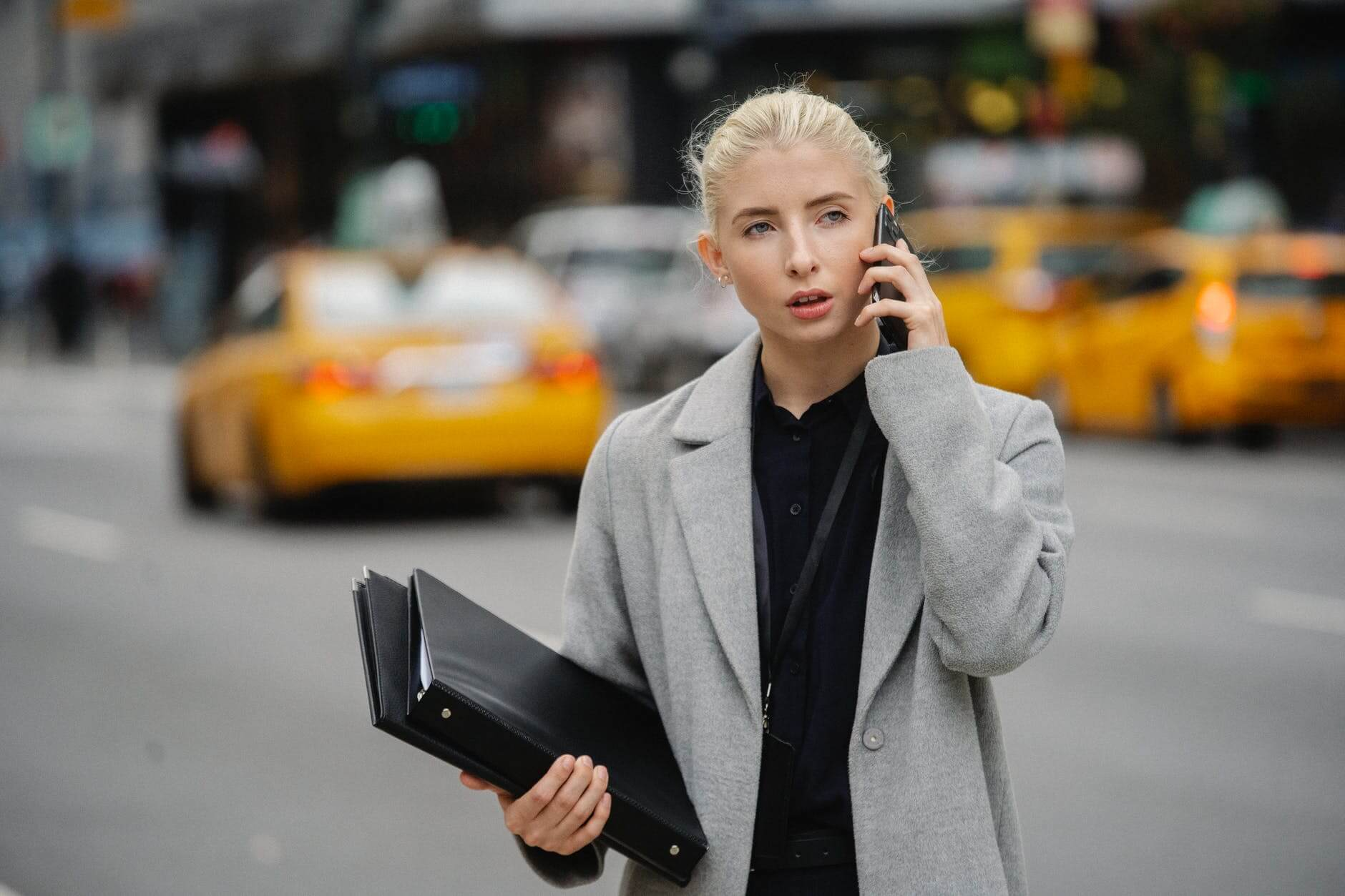 concentrated businesswoman talking on smartphone on street