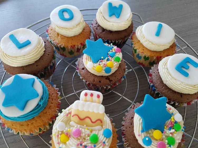 verjaardagscupcakes met botercème en blauwe belettering