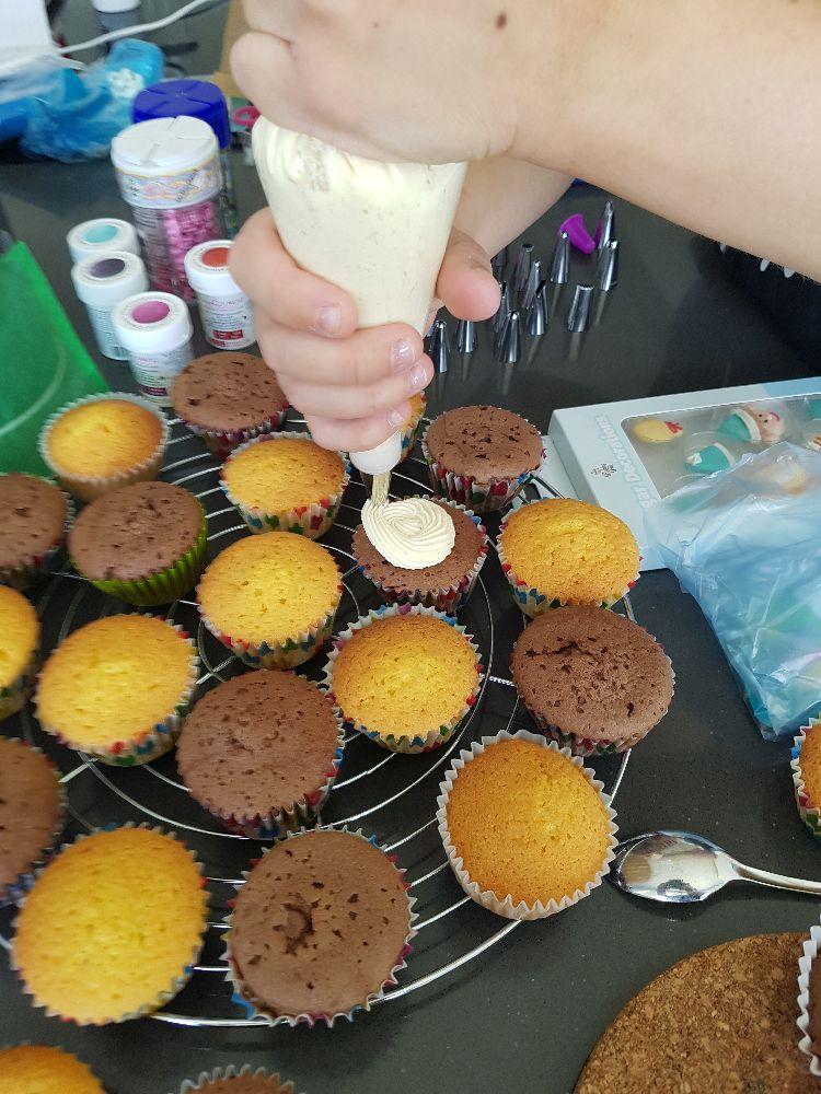 vanille en chocolade cupcakes en de spuitzak gevuld met botercrème