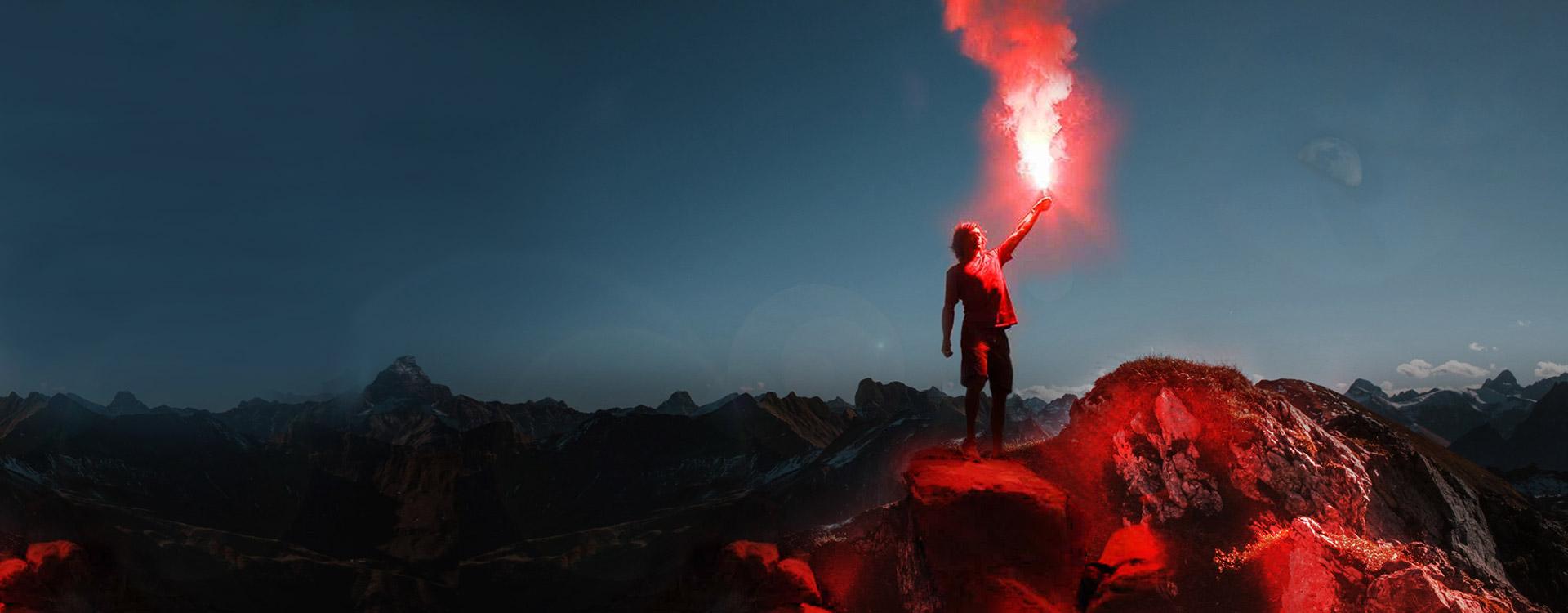 Man gebruikt fakkels bovenop berg om gevonden te worden