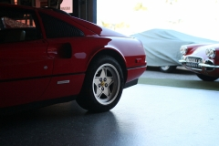 Ferrari-328-behind-pointing-out-from-Garage-77-Corvette-C1