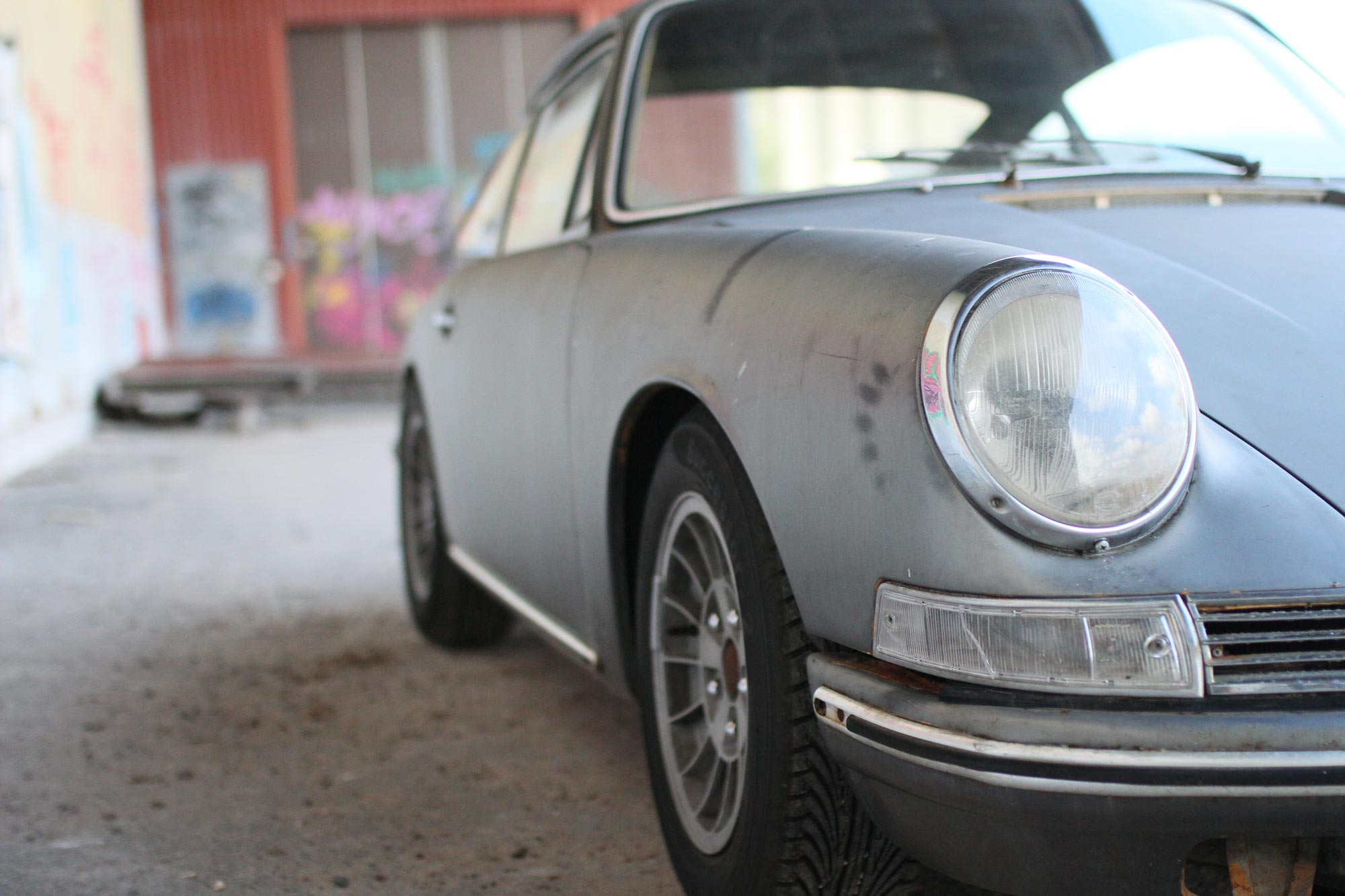 patina porsche and its headlights taken from the right side