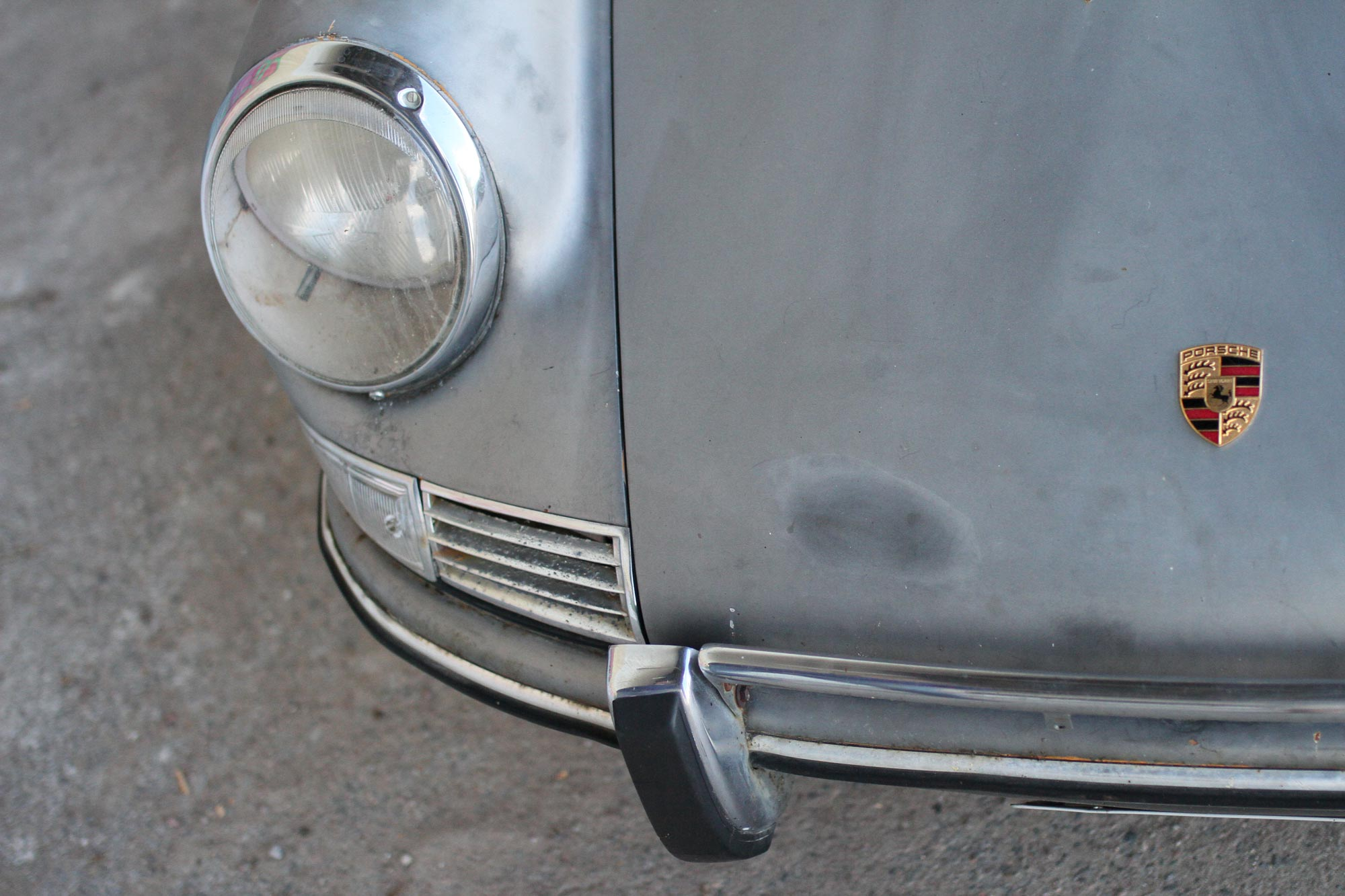 The Porsche badge in the front of the car together with the headlights on a patina 912