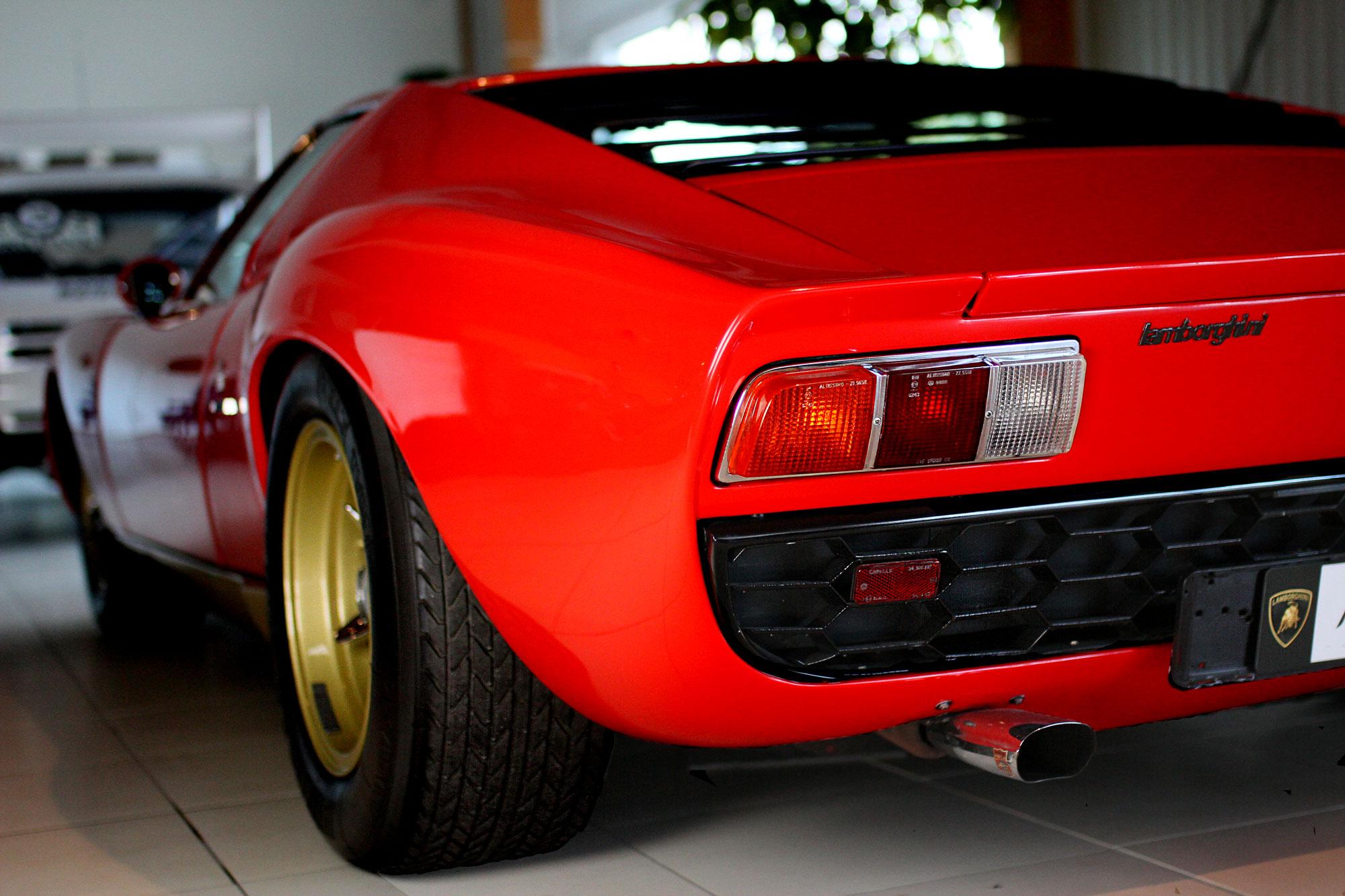 Röd Lamborghini Miura med guld fälgar som står på ett gråvitt klinkers golv i ett garage