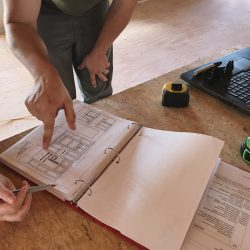 detail-photo-of-two-peoples-hands-reviewing-cabinet-elevations-for-a-kitchen-remodel_t20_WQZQO1