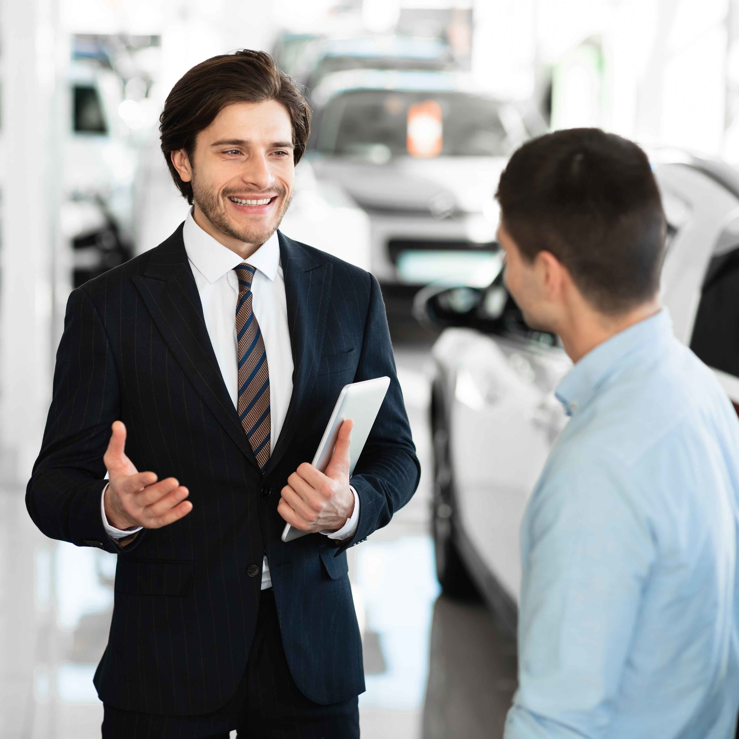 car-dealer-talking-with-clients-selling-them-autom-XJSXJLH