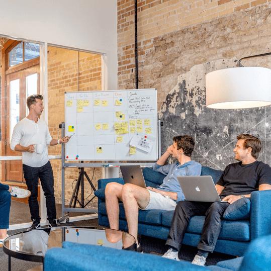 Digital marketing bureaus ansatte holder møde med tavle