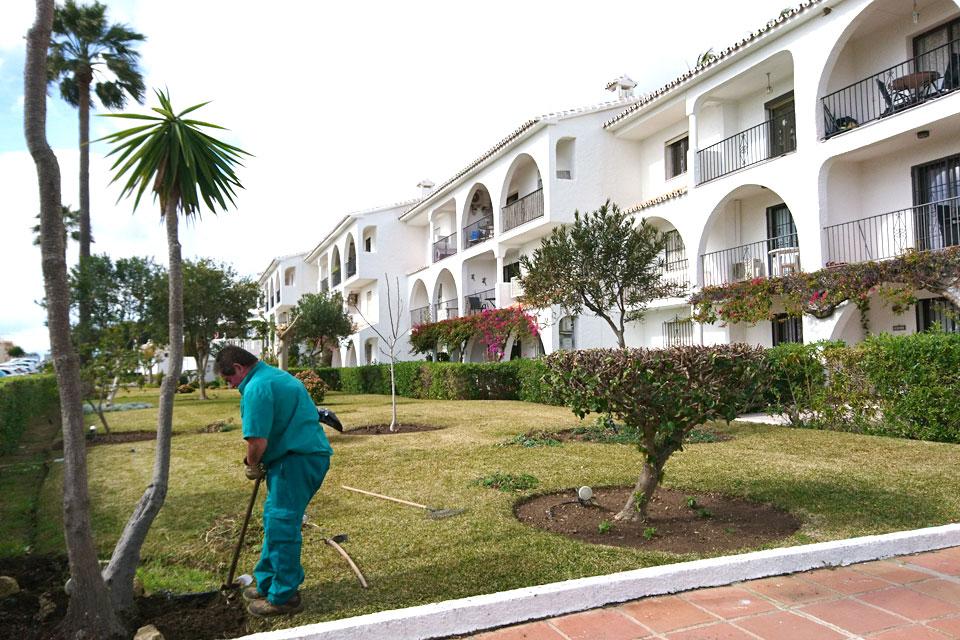 Садовник ухаживает за растениями в саду жилищного комплекса коста-дель-соль