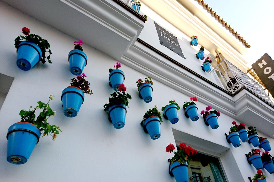 Белоснежные стены гостиницы украшены голубыми горшками с цветущей геранью