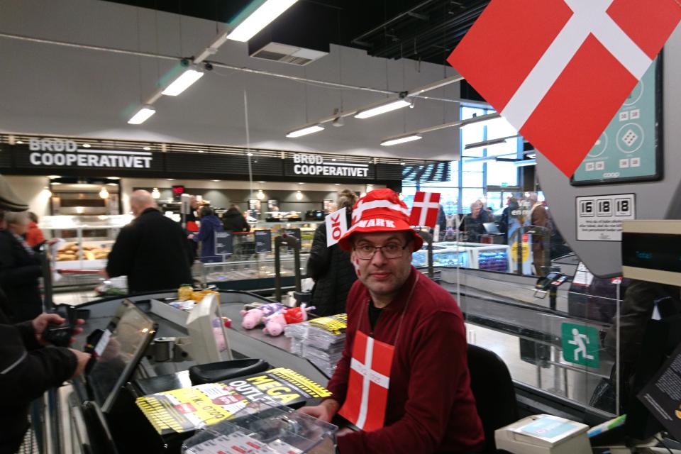 Кассир, разукрашенный флажками и с флажком на щеке в местном супермаркете