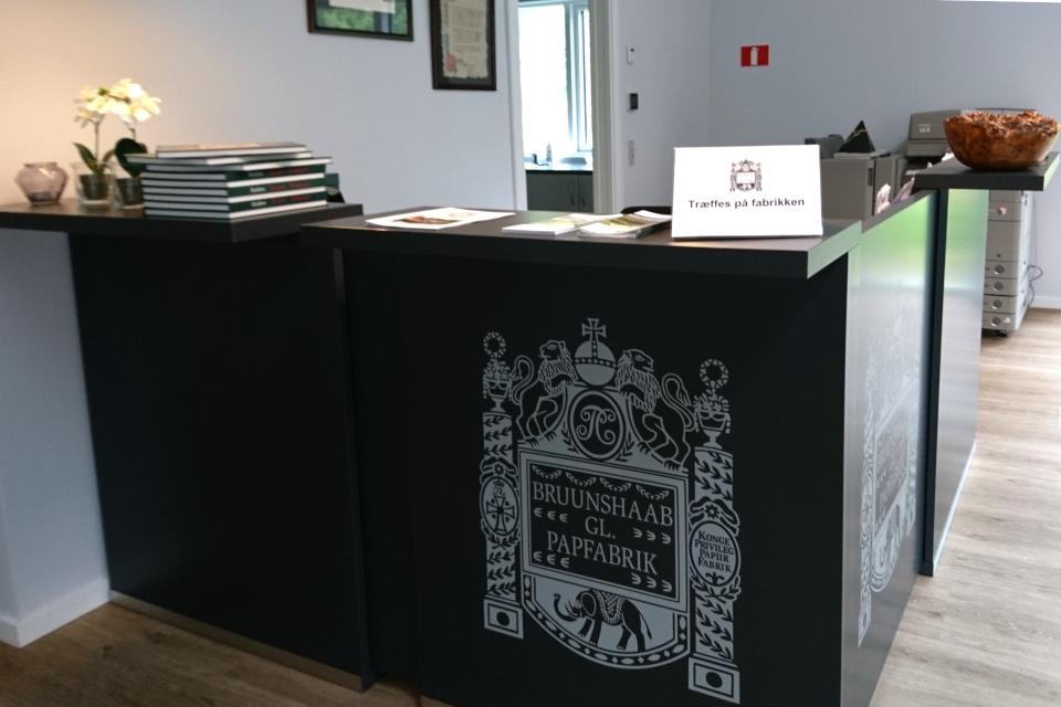 Административная стойка офиса, украшенная фамильным гербом династии Брунсхоб