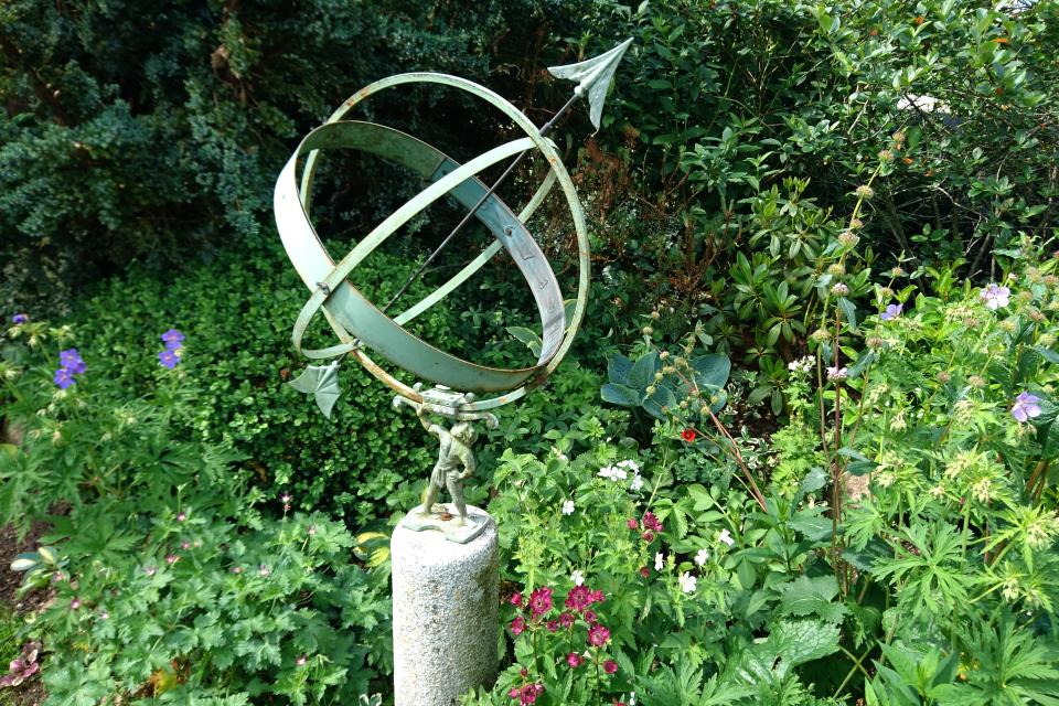 Солнечные часы на газоне с астраниями и геранями