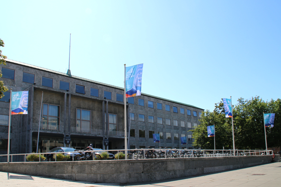 Здание ратуши Орхуса, украшенное флагами с рекламой регаты больших парусников 2019.