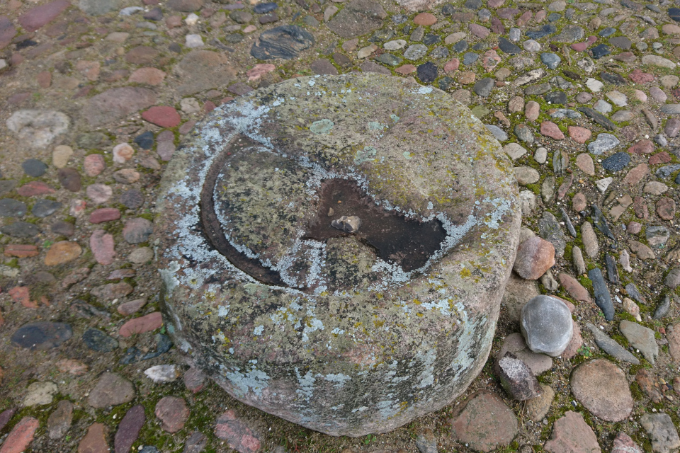Камень с символом монастыря Витскол во дворе зданий.