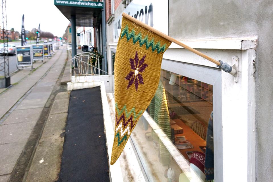 Вывеска магазина рукоделия, связанная крючком с мотивом пуансетии