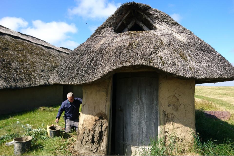 Доброволец восстанавливает стену домика из смеси глины с навозом