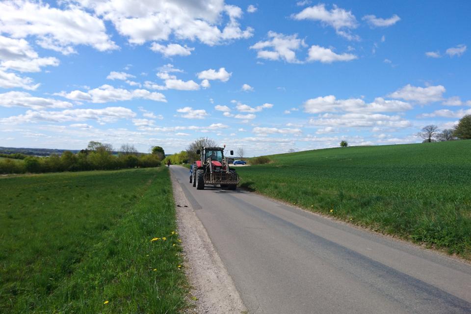 Дорога через поля на холмах. В глубине видна парковка