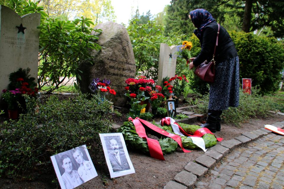 Цветы возле мемориального камня Советским солдатам и фотографии родных